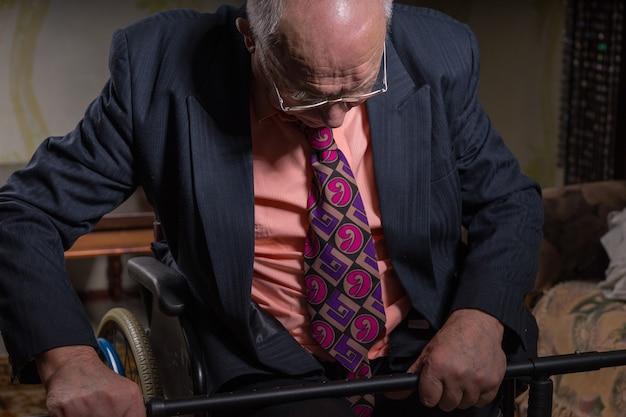 Feche o velho pensativo em trajes formais, sentado em sua cadeira de rodas, segurando sua bengala e olhando para baixo.