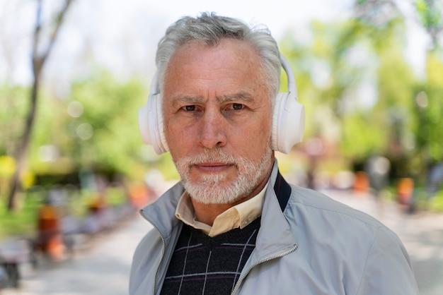 Feche o velho usando fones de ouvido