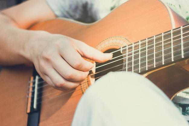 Feche o violão com a mão do guitarrista no parque jovem sentado no banco do parque