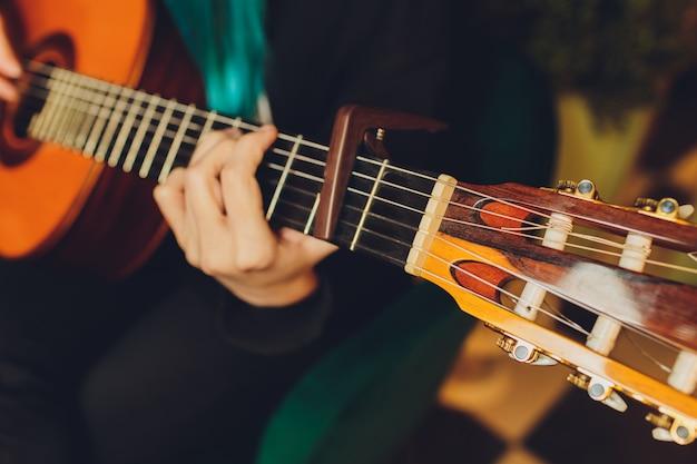 Feche o violão nas mãos do músico no quarto escuro.