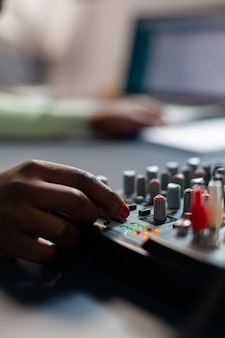 Feche o vlogger afro fazendo ajustes de som. falando durante a transmissão ao vivo, blogueiro discutindo no podcast usando fones de ouvido.