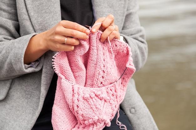 Feche og uma jovem mulher casada, vestida com um casaco moderno, tricotando um chapéu rosa com agulhas de tricô contra o mar em um dia ensolarado de outono. conceito de vida e trabalho criativo freelance