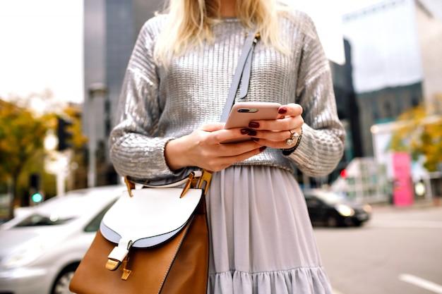 Feche os detalhes da moda da cidade de uma mulher elegante e elegante vestindo um suéter prateado, saia de seda, bolsa de couro de luxo e óculos escuros, posando na rua de nova york perto de centros de negócios, toque em seu telefone.