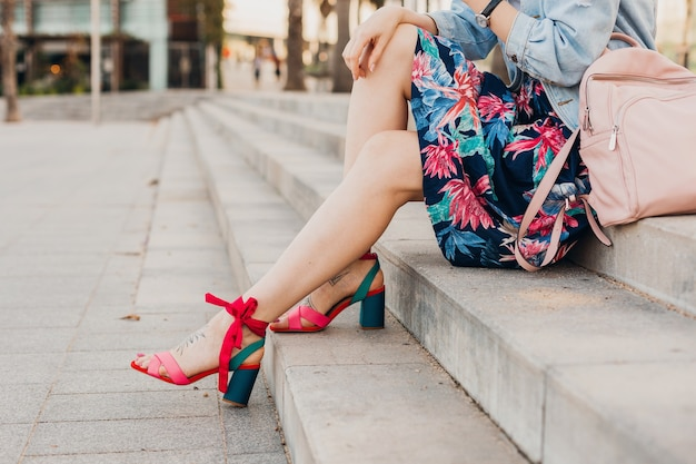 Feche os detalhes das pernas com sandálias rosa de mulher sentada na escada em uma rua da cidade com saia estampada elegante e mochila de couro, tendência do verão