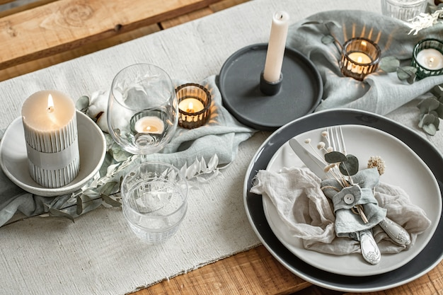 Feche os detalhes de uma configuração de mesa festiva com um conjunto de talheres, um prato e velas em castiçais.