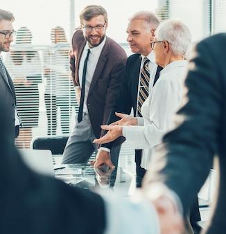 Feche os empresários apertando as mãos em pé no escritório