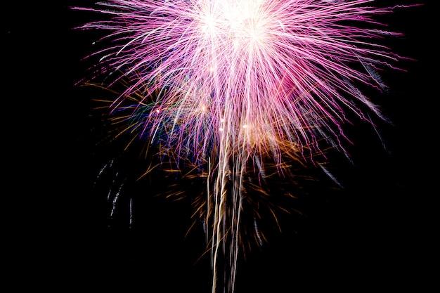 Feche os fogos de artifício que sobem do chão para o céu e quebram as cores.