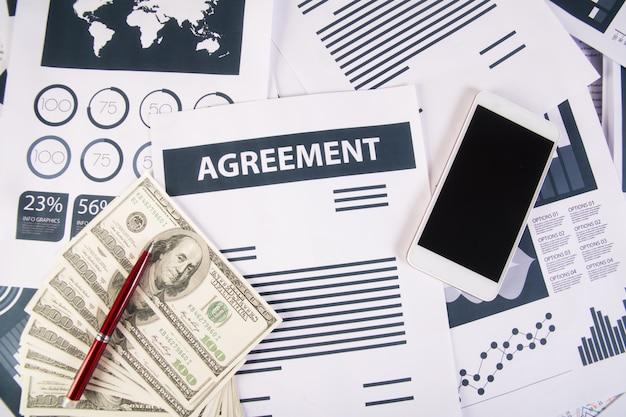 Feche os gráficos e gráficos do smartphone money no local de trabalho no escritório. conceito de negócios.