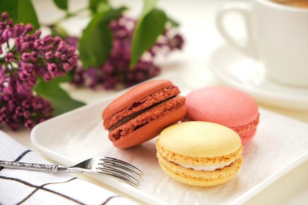Feche os macarons e a xícara de café em uma mesa com flores lilás