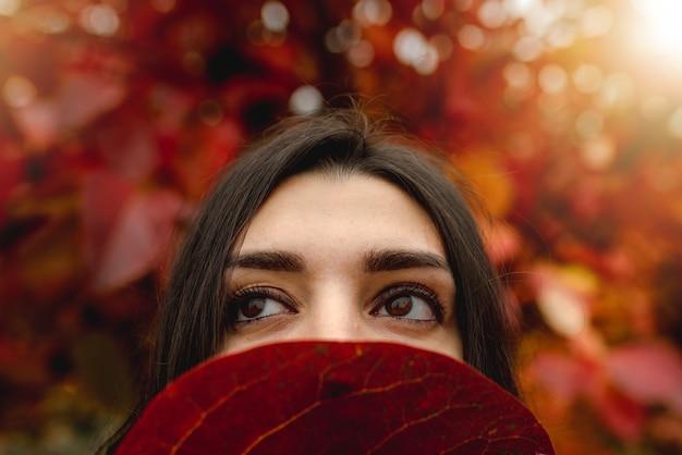 Feche os olhos de mulher jovem cobrindo metade do rosto com uma folha vermelha. temporada outono, conceito de cor vermelha.