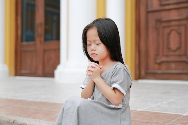 Feche os olhos menina sentada e rezando