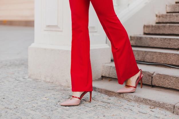 Feche os pés com sapatos nos saltos de uma bela mulher sexy estilo rich business em um terno vermelho andando na rua da cidade, tendência da moda primavera verão