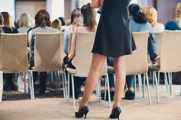 Feche os pés da moda usando sapatos bege contemporâneos nos saltos altos internos. conceito da moda.