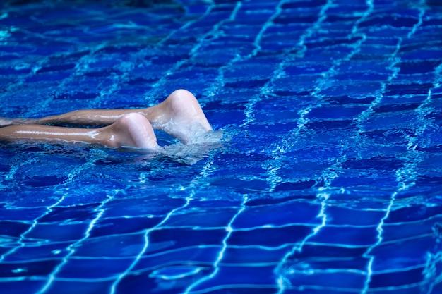 Feche os pés de criança na piscina, flutuando na água azul refrescante e azulejo.