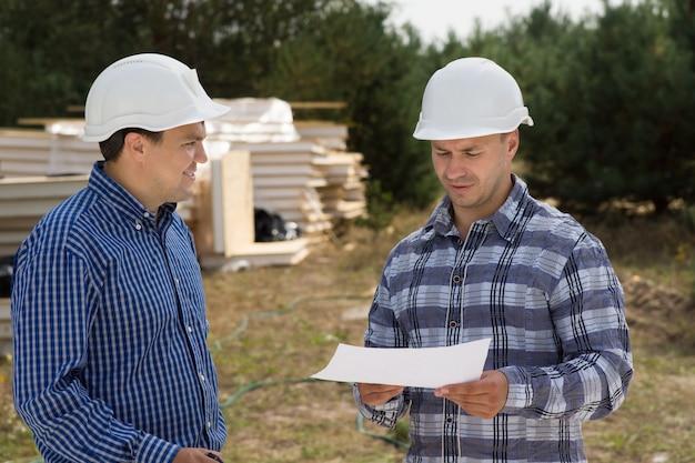 Feche os planejadores de construção da meia-idade, discutindo o andamento da construção no local.