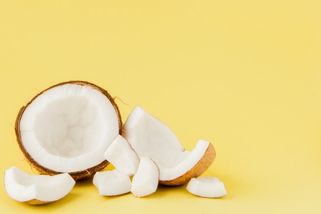 Feche pedaços de coco fresco isolados em um amarelo