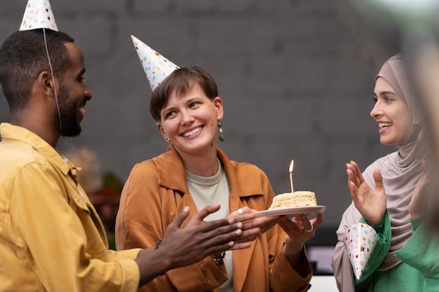 Feche pessoas comemorando com bolo