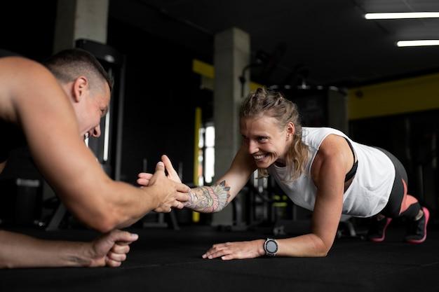 Feche pessoas felizes treinando juntas
