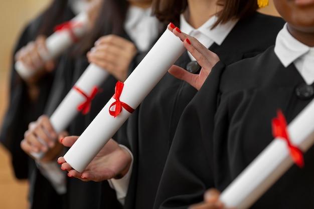 Feche pessoas se formando com diplomas