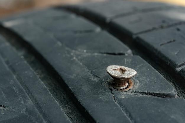 Feche pregos de parafusos de metal bordados em pneus