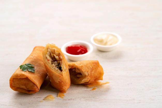 Feche rolinhos primavera fritos, populares como lumpia (rebung) ou popia. servido na mesa de pedra, isolado com espaço para texto