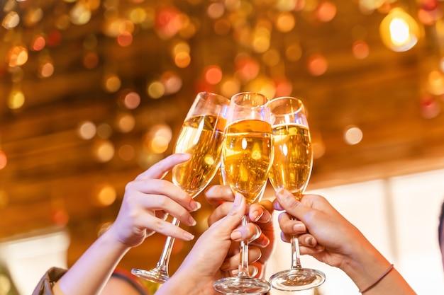 Feche taças de taças de champanhe tilintando com a festa iluminada com a bebida de champanhe