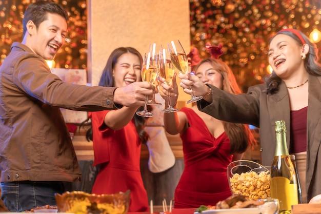 Feche taças de taças de champanhe tilintando com iluminação e brilho festa do amigo asiático