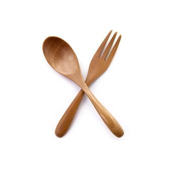 Feche um garfo de madeira e uma colher isolados no fundo branco