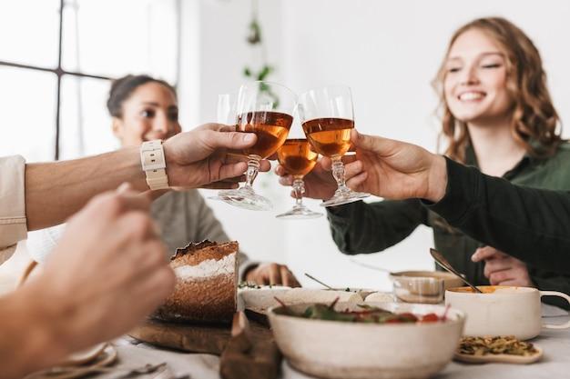 Feche um grupo de amigos internacionais sentados à mesa com taças de vinho nas mãos