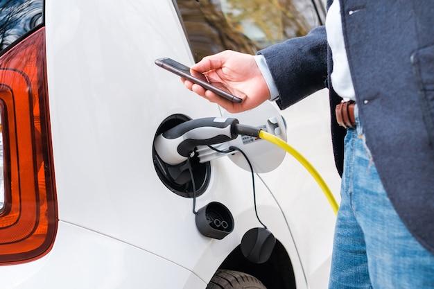 Feche um homem de terno em pé perto do carro elétrico carregando e usando seu smartphon