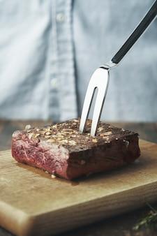 Feche um pedaço de carne grelhada em uma placa de madeira com um grande garfo de aço