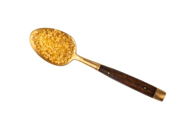 Feche uma colher de metal dourado vintage com cabo de madeira cheio de açúcar mascavo de cana-de-açúcar, isolado na vista superior branca, diretamente acima Foto Premium
