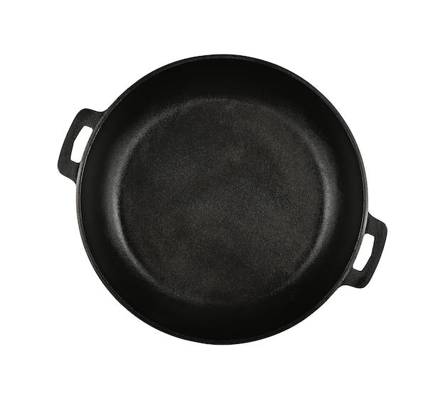 Feche uma frigideira de ferro fundido preto vazia isolada no fundo branco, vista superior elevada, diretamente acima