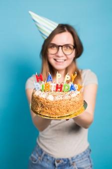 Feche uma garota engraçada turva positiva de óculos e saudação de chapéu de papel segurando um bolo de feliz aniversário nas mãos em pé sobre uma superfície azul