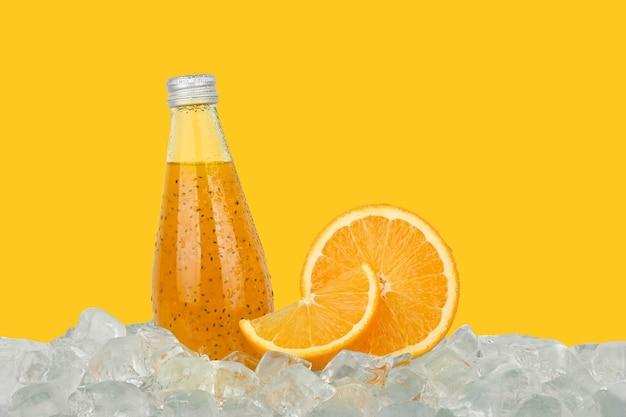 Feche uma garrafa de vidro de suco de laranja gelado com sementes de chia e meia laranja cortada em cubos de gelo isolados em um fundo amarelo, vista lateral de baixo ângulo