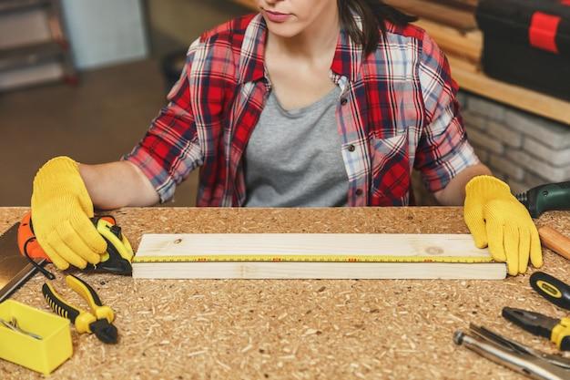 Feche uma jovem caucasiana de cabelos castanhos em uma camisa xadrez, camiseta cinza, luvas amarelas trabalhando em uma oficina de carpintaria em uma mesa de madeira com ferramentas diferentes, medindo o comprimento da barra por fita métrica