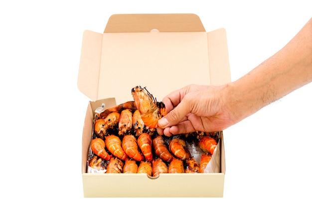 Feche uma mão humana pegar um camarão grelhado em uma caixa de papel isolada no fundo branco.