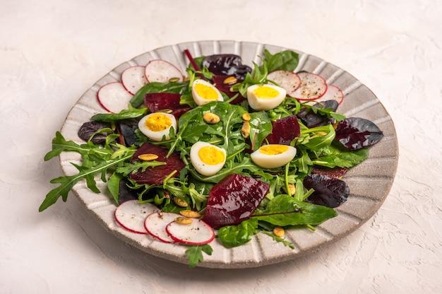 Feche uma salada caseira de ovos de codorna, beterraba cozida, rabanete, rúcula e manjericão com azeite de oliva em um fundo claro, copie o espaço