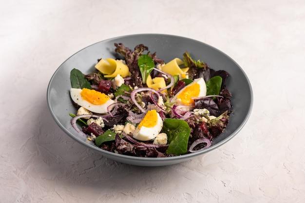 Feche uma salada caseira de ovos de galinha, beterraba cozida, queijo, rúcula e manjericão com azeite de oliva em um fundo claro, foco seletivo, espaço de cópia