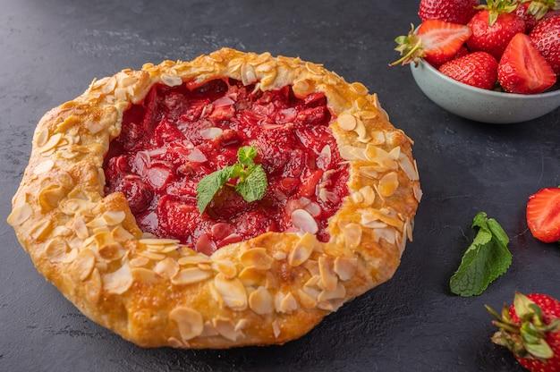 Feche uma torta de pudim de verão caseira com morangos, hortelã e pétalas de amêndoa