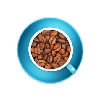 Feche uma xícara cheia de grãos de café torrados em um pires azul isolado no fundo branco, vista superior elevada, diretamente acima