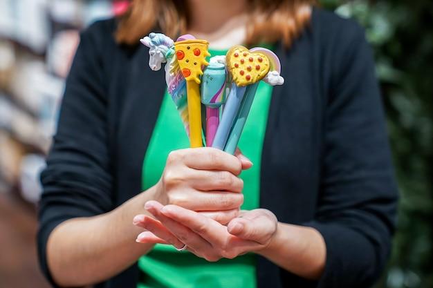 Feche várias canetas coloridas na mão de uma garota
