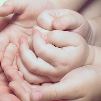 Fechem as mãos das crianças. nova família, amor materno e conceito de proteção ao bebê.