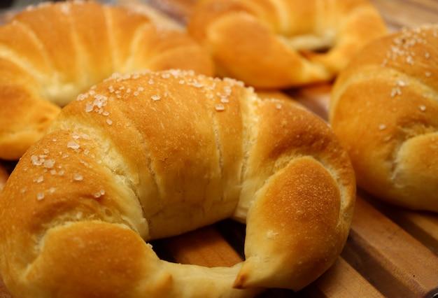 Fechou croissants revestidos de açúcar assados frescos na bandeja de madeira