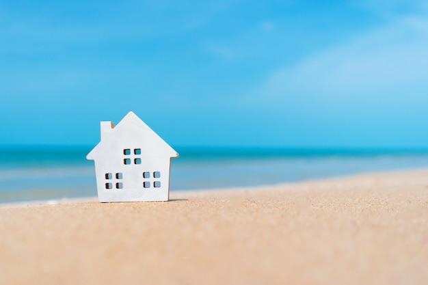 Fechou minúsculos modelos domésticos na areia com luz solar e fundo de praia.