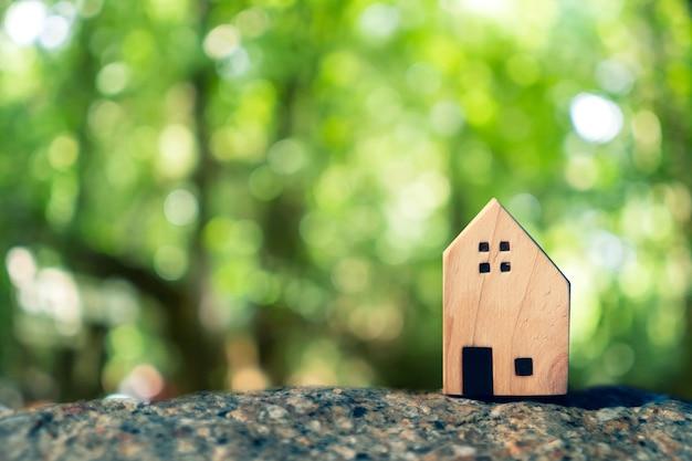 Fechou o minúsculo modelo doméstico no piso ou placa de madeira com fundo de bokeh verde luz solar. deam life tem casa própria para morar ou conceito de investimento.