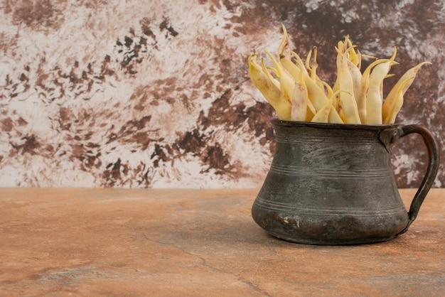 Feijão amarelo cru na tigela e na superfície laranja.
