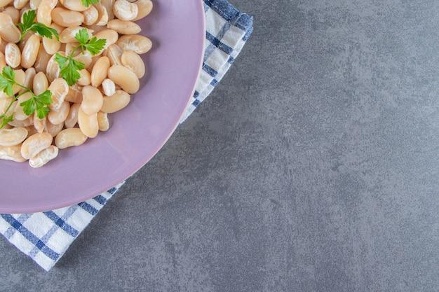 Feijão branco com pepino em um prato ao lado do brunch de salsa em uma toalha na superfície de mármore