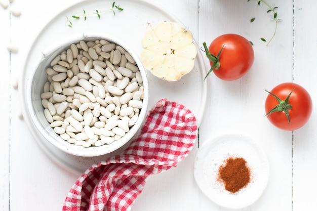 Feijão branco cru em uma tigela perto de tomates secos