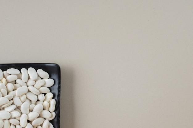 Feijão branco em bandejas de comida em concreto.